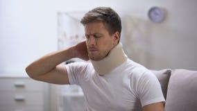 Homem desagradado no colar cervical da espuma que sente de repente a dor no pescoço, traumatismo video estoque