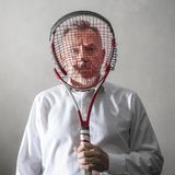 Homem desanimado que olha sua raquete de tênis quebrada fotos de stock