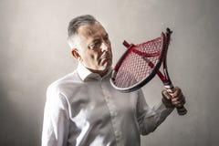Homem desanimado que olha sua raquete de t?nis quebrada fotografia de stock royalty free