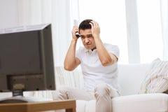 Homem desapontado que olha a tevê em casa Fotografia de Stock