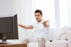 Homem desapontado que olha a tevê em casa Imagens de Stock