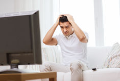 Homem desapontado que olha a tevê em casa Foto de Stock Royalty Free