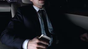 Homem desapontado que senta-se no banco traseiro do carro e que usa o telefone esperto, cidade da noite filme