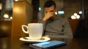 Homem desapontado que senta-se no café e que olha o telefone, amiga de espera video estoque