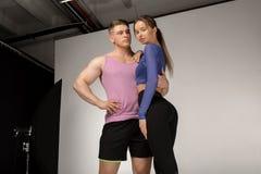 Homem descamisado atlético novo e mulher bonita no sportswear preto imagens de stock royalty free