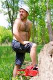 Homem descamisado com uma serra de cadeia que limpa sua testa Fotografia de Stock
