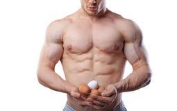 Homem descamisado do atleta que mostra o copo com os ovos no fundo branco isolado Imagem de Stock Royalty Free