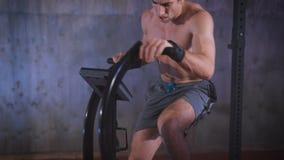 Homem descamisado muscular novo que faz o exercício na bicicleta no gym vídeos de arquivo