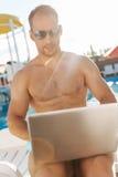 Homem descamisado muscular que datilografa um email em seu portátil foto de stock royalty free