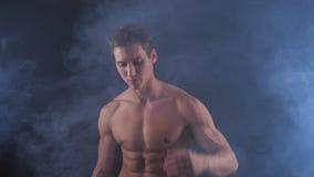 Homem descamisado muscular que levanta no fundo escuro, com fumo em torno dele vídeos de arquivo