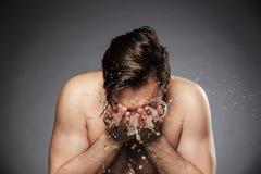 Homem descamisado novo do retrato que lava sua cara com água fotos de stock
