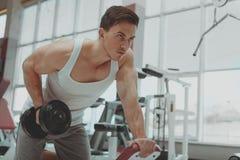 Homem descamisado rasgado que exercita com pesos no gym imagens de stock royalty free
