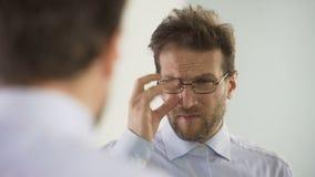 Homem descontentado com seus vidros e pensamento sobre o procedimento da correção da visão video estoque