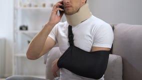 Homem descontentado no colar cervical da espuma e no telefone de fala do estilingue do braço, problema video estoque