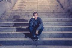 Homem desempregado desesperado novo na roupa ocasional abandonada perdida na depressão que senta-se nas escadas concretas à terra imagens de stock