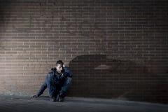 Homem desesperado novo que o trabalho perdido perdeu na depressão que se senta na esquina da rua à terra imagens de stock