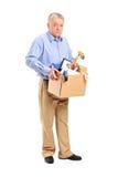Homem despedido que carreg uma caixa de artigos pessoais fotografia de stock royalty free