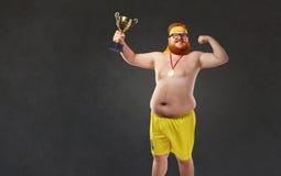Homem despido gordo com um copo do ` s do campeão em suas mãos fotos de stock