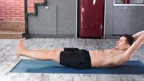 Homem desportivo com o corpo atlético magro perfeito que aprecia praticando a opinião lateral do exercício da ioga em casa filme