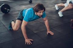 Homem desportivo em rastejamentos azuis da camisa de T no assoalho do Gym imagens de stock