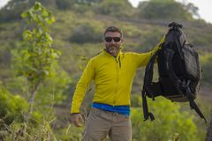 Homem desportivo feliz e atrativo novo do caminhante com a trouxa trekking que caminha na fuga de apreciação livre do curso do se imagens de stock