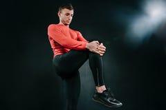 Homem desportivo novo que veste o sportswear vermelho e que estica seu pé após um exercício pesado no fundo escuro Athleti consid Fotografia de Stock