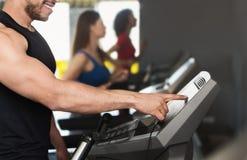 Homem desportivo que ajusta a velocidade na escada rolante no gym imagens de stock