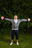Homem desportivo que mantém pesos vermelhos com braços estendido Fotos de Stock