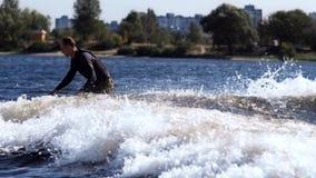 Homem desportivo que wakeboarding no rio Vigília nova do desportista que surfa em ondas video estoque