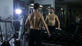 Homem desportivo 'sexy' novo que está na frente do espelho grande no salão que faz exercícios com suas mãos com os pesos, novos filme