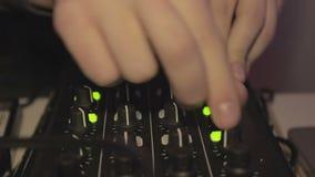 Homem DJ da dança que está nos botões do misturador, da empurrão e do giro apreciação vídeos de arquivo