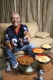 Homem do African-American com o telecontrole apontado no visor. Fotografia de Stock Royalty Free