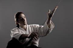 Homem do Aikido que olha o katana (espada) Foto de Stock