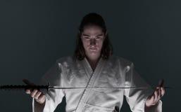 Homem do Aikido que olha o katana (espada) Fotos de Stock Royalty Free
