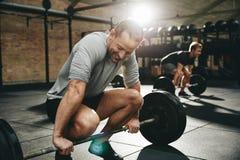 Homem do ajuste que tenta levantar peso no gym foto de stock royalty free