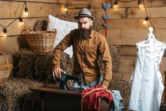Homem do alfaiate perto da máquina de costura foto de stock royalty free