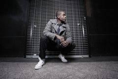 Homem do americano africano que squatting na noite Imagem de Stock Royalty Free
