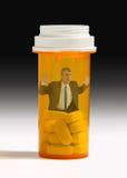 Homem do apego do comprimido de dor prendido na garrafa de comprimido Foto de Stock Royalty Free