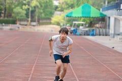 Homem do atleta do corredor que corre no trackrace no estádio Movimentar-se para o conceito saudável imagem de stock