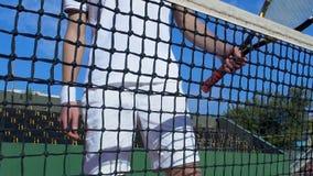 Homem do atleta no sportswear branco que está a rede próxima com raquete, treinamento do tênis video estoque