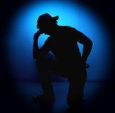 Homem do balancim da silhueta que levanta no fundo azul Fotografia de Stock Royalty Free