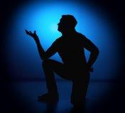 Homem do balancim da silhueta que levanta no fundo azul Fotografia de Stock