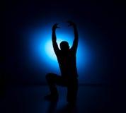Homem do balancim da silhueta que levanta no fundo azul Imagem de Stock Royalty Free