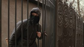 Homem do bandido na máscara preta e capa com rastejamentos do bastão de beisebol através da malha da cerca filme