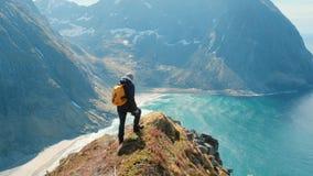 Homem do caminhante com uma posição na borda da montanha em Noruega dentro com forte vento vídeos de arquivo