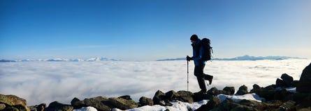 Homem do caminhante no monte rochoso no vale nevoento com nuvens brancas, as montanhas nevados e o fundo do céu azul fotografia de stock