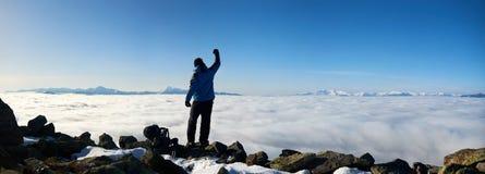 Homem do caminhante no monte rochoso no vale nevoento com nuvens brancas, as montanhas nevados e o fundo do céu azul foto de stock royalty free