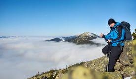 Homem do caminhante no monte rochoso no vale nevoento com nuvens brancas, as montanhas nevados e o fundo do céu azul imagem de stock royalty free