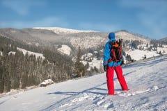 Homem do caminhante que descansa nas montanhas do inverno, estando em um coberto de neve Fotografia de Stock