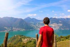Homem do caminhante que está de admiração uma opinião do cume que olha para fora sobre escalas de montanhas distantes e de vales  fotografia de stock